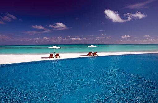 Blick auf den Pool und Strand, Atmosphere Kanifushi Maldives