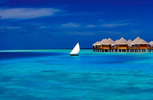 Water Villas mit Dhoni, Blick vom Meer, Baros Maldives