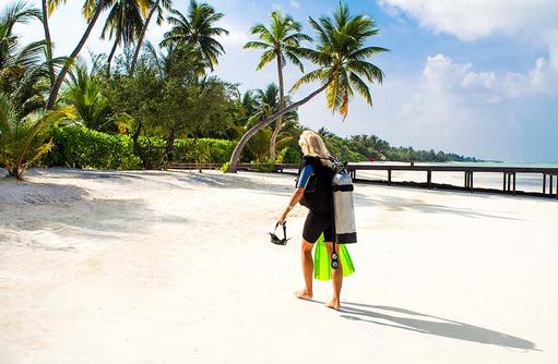 Taucher am Strand, Canareef Resort, Malediven