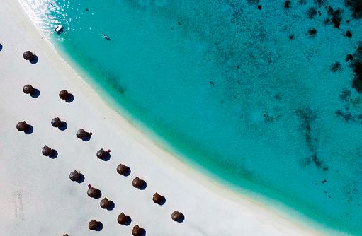 weißer Sandstrand von oben mit Sonnenschirmen, Constance Moofushi Resort, Malediven