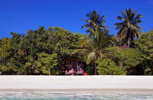 Sonnenbaden am Strand, Komandoo Island Resort, Maldives