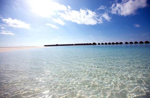 Panorama mit Wasservillen am Horizonten, glitzerndes Wasser I LUX South Ari Atoll