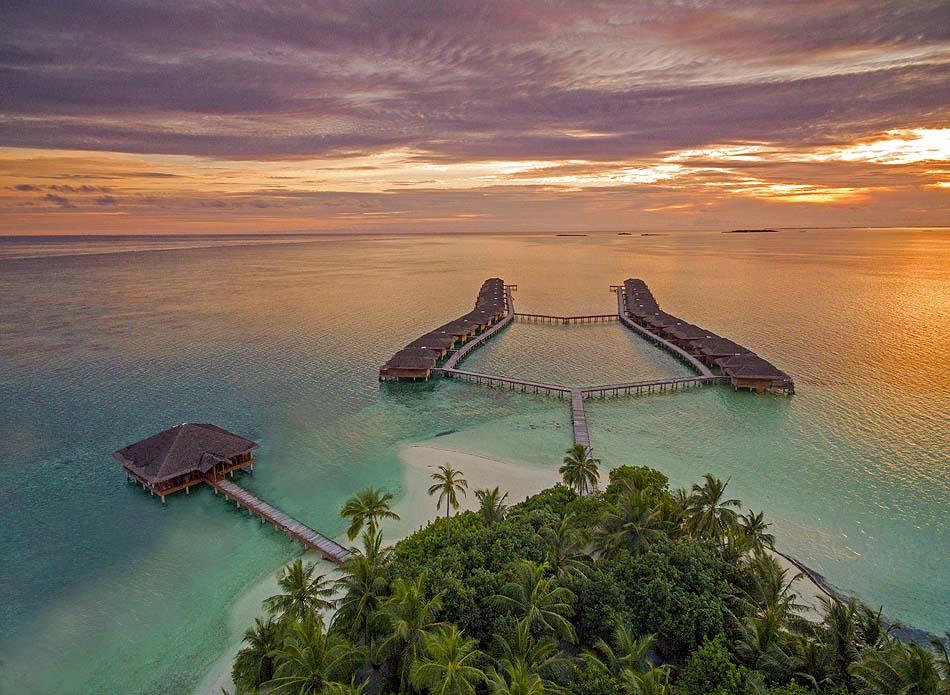 Blick auf die Wasservillen im Abendrot, Medhufushi Island Resort, Maldives